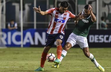 Teo Gutiérrez cubre un balón ante el asedio de un jugador del Cali.
