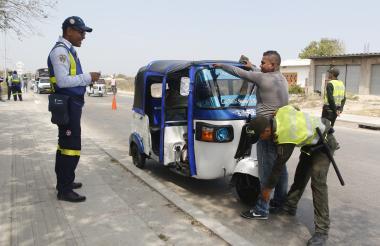 Un policía requisa a un conductor de motocarro en un retén del Tránsito Municipal.