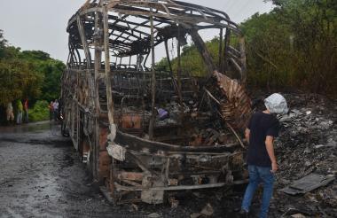 Una persona camina frente al bus que quedó completamente incinerado.