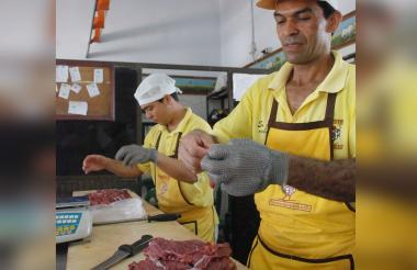 Vendedores preparando carne de res para el comercio.