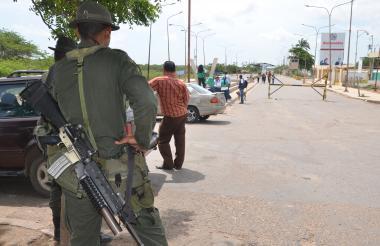 Dos uniformados vigilan el paso de los viajeros en Paraguachón, La Guajira. Al fondo se aprecia una de las calles del paso fronterizo, poco transitada por viajeros.