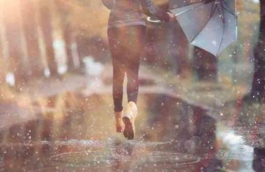 Una mujer corre bajo un fuerte aguacero.