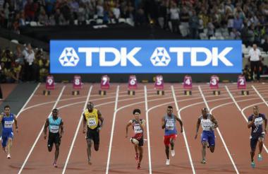 Palomeque (pantaloneta roja) corriendo junto a Bolt.