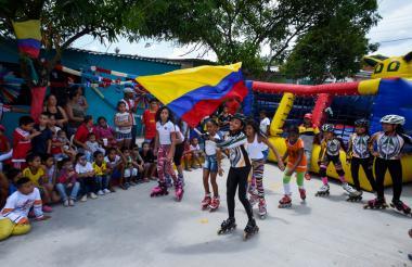 Niñas del club de patinaje del barrio 7 de Agosto mientras realizan una muestra deportiva con el tricolor