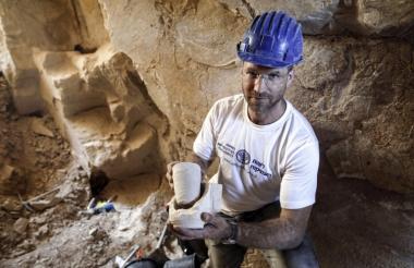 Un arqueólogo exhibe una de las piezas halladas en la excavación.