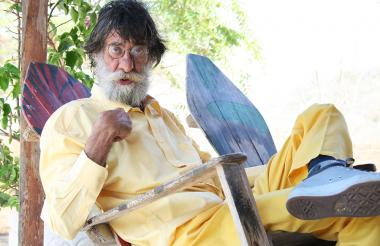 El artista Aníbal Tobón sentado en una mecedora.