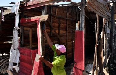 Un residente del barrio ayuda a desarmar una casa.