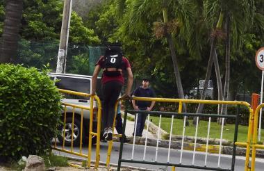 Un joven salta sobre una valla para atravesar la vía.
