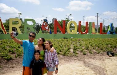 Noel Sibada y sus hijos se toman una selfie frente al letrero de bienvenida a Barranquilla.