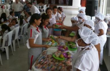 Estudiantes realizando fila para recibir alimentos.