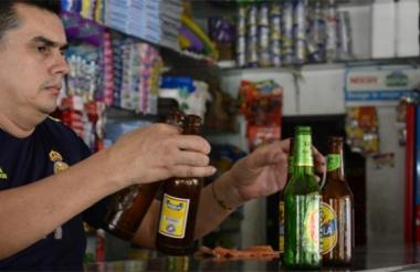 Un tendero recoge envases de cerveza en una tienda de barrio.