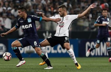 Maycon, del Corinthians, disputa el balón con Diego González del Racing Club.