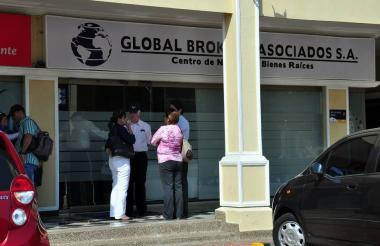 Personas en la entrada de una de las oficinas donde funcionaba la empresa Global Brokers.