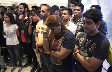 Grupos de opositores escuchan apesadumbrados en la sede de la Mesa de la Unidad Democrática los resultados de la jornada del domingo.