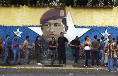 Un grupo de personas hace cola para votar, ante una imagen del fallecido presidente Hugo Chávez.