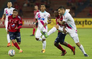El defensa central del Junior, Jhonatan Ávila, luchando el balón con Caicedo.