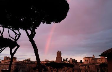 Muestra un arcoiris sobre la ciudad de Roma durante una puesta de sol.