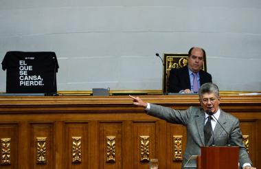 """El opositor Henry Ramos (d) señala la silla de su compañero Guevara, que aparece con la leyenda """"el que se cansa, pierde"""". Observa Julio Borges."""