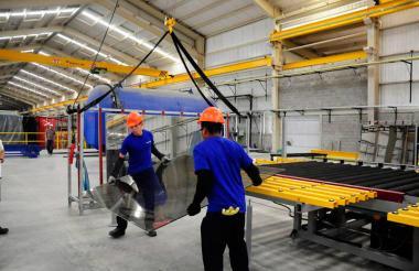 Trabajadores sostienen el vidrio templado para ventanería en el Parque Industrial de Tecnoglass en Barranquilla.