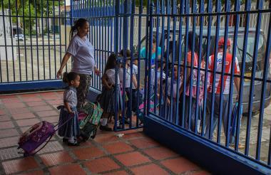 Varios niños salen del colegio para abordar el carro escolar que los lleve a casa.