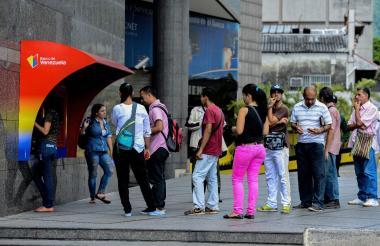 Personas tratando de retirar dinero de un cajero ATM EN Caracas luego de declarar al país en defaut.