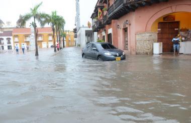 Un automóvil transita por las calles inundadas en el sector Amurallado de Cartagena.