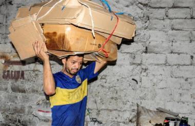 Un hombre carga varias cajas de cartón para reciclar.