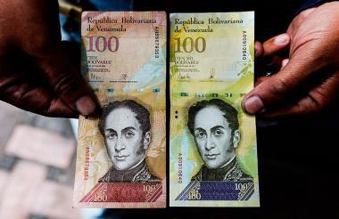 Un hombre muestra el nuevo billete de 100.000 nuevos bolívares (der.) al que compara con el de 100, para mostrar el parecido entre ambos billetes.