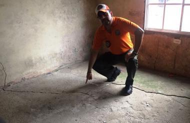 Un hombre señala la grieta en el suelo.