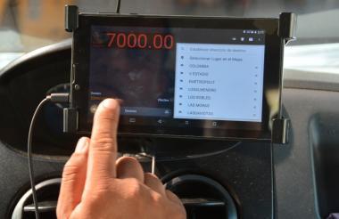 Con su dedo índice un taxista señala la tablet en la que funciona el taxímetro.