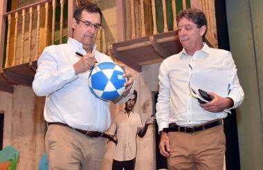 Adolfo Meisel y Bruce Mac Master firman un balón como símbolo del pacto.