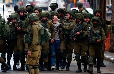 Un manifestante palestino es detenido por soldados israelíes durante los enfrentamientos de ayer en Hebrón, por la decisión de EEUU sobre Jerusalén.
