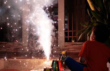 Un niño observa las llamas que salen de un elemento pirotécnico.