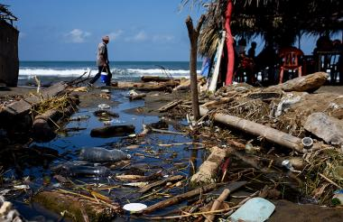 Las aguas de un canal lleno de basuras se mezclan con el agua del mar.