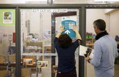 Una mujer pone un cartel de información para la elección durante la instalación de una mesa de votación en la escuela Prat de la Mata.
