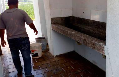 Trabajador haciendo limpieza de uno de los baños.