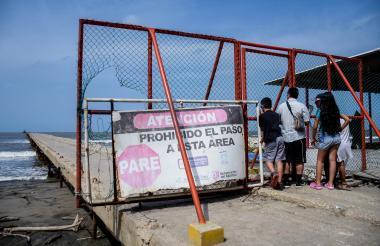 Cuatro turistas observan detrás de la valla de restricción lo que queda el muelle.