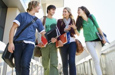 Grupo de jóvenes estudiantes universitarios saliendo de clases.