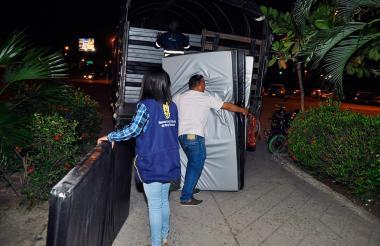 Dos ciudadanos suben colchonetas a un camión rumbo al coliseo de combate de Cartagena.