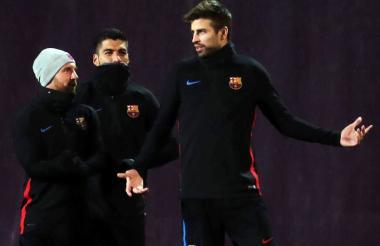 Gerard Pique dialoga con Lionel Messi y Luis Suárez.