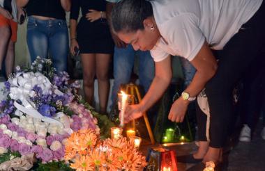 Un familiar de uno de los uniformados fallecidos coloca una vela durante el homenaje.