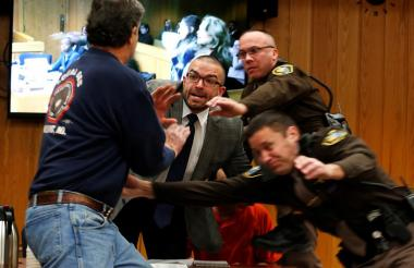 Policías intentan detener al padre de familia que va a en busca de Nassar.