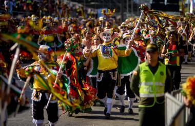 Un agente de la Policía custodia el desfile de la Gran Parada, mientras un grupo de Garabato baila.