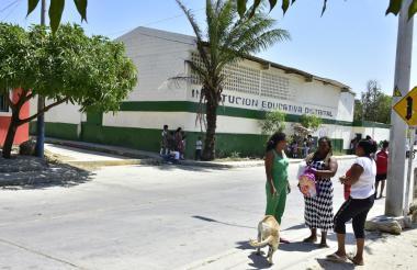 Tres acudientes se reúnen diagonal a la primera sede de la Institución Educativa Distrital La Esmeralda.