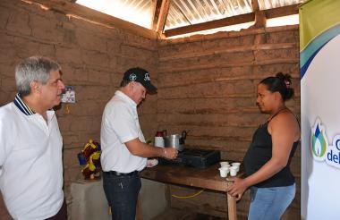 El gobernador del Cesar, Franco Ovalle, enciende una estufa a gas.  Lo observan el gerente de Gases del Caribe, Ramón Dávila, y una nueva usuaria.
