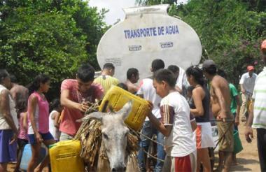 Personas se abastecen de agua desde un carrotanque.