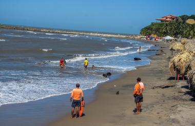 Varios turistas se bañan en las playas de Salgar, mientras dos salvavidas los observan.