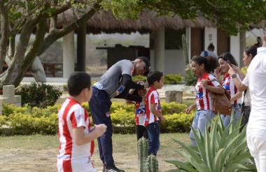 El técnico Alexis Mendoza  le firma gustosamente la camiseta del Junior a un pequeño aficionado.