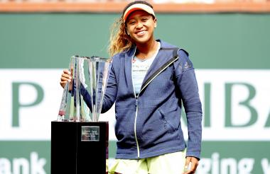 Naomi Osaka posa feliz con el trofeo de campeona.