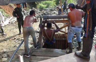 Trabajadores de la mina tratan de auxiliar a su compañeros.